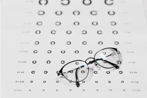 Pair of eyeglasses sitting on top of black and white eye exam.
