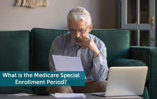 Elderly man sitting on a green couch looking at a piece of paper in front of an open laptop, wondering how Medicare Special Enrollment Period works.